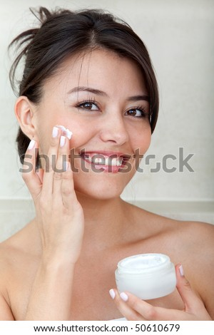 Beauty female portrait putting cream on her face - stock photo