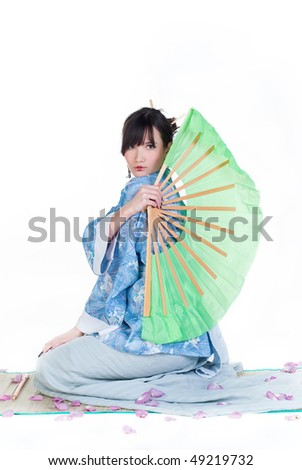beauty geisha in blue kimono sit on mat with big green fan isolated on white background
