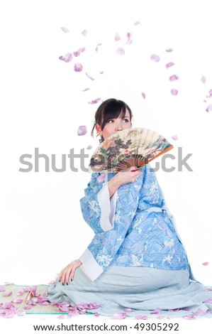 beauty geisha in blue kimono sit on mat with fan isolated on white background