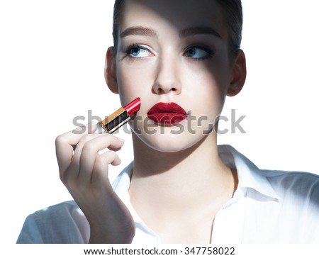 Beauty girl Applying red lipstick /photo composition of brunette girl, close-up of an attractive girl of the European appearance in a white shirt on a white background. - stock photo