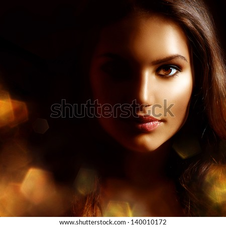 Beauty Girl Dark Portrait with Golden Sparks. Mysterious Woman Face. Darkness. Isolated on Black - stock photo