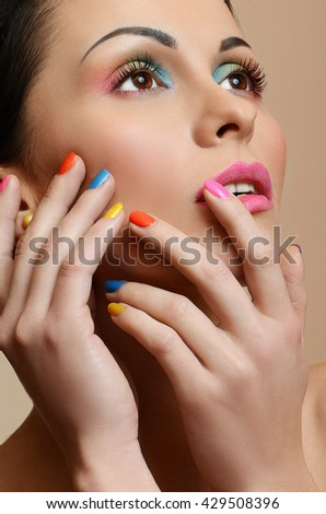 Beauty Girl Face with Colorful Nail polish. Colourful Studio Shot of young Woman