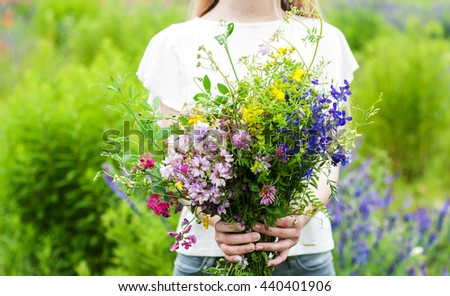 Beauty girl holding a bouquet of wildflowers - stock photo