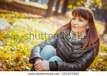 beauty girl in autumn park sitting on a carpet of yellow leaves - stock photo