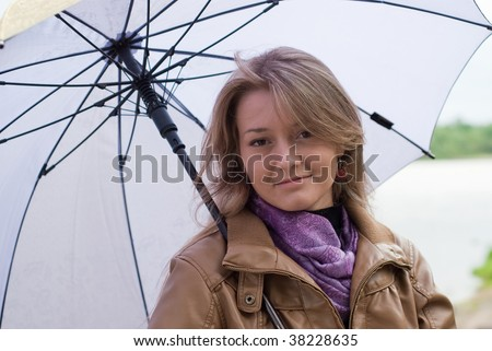 beauty girl in brown jacket and  with violet umbrella on the river background - stock photo