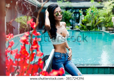 Beauty girl in park with red flowers,pretty face woman with lotus,fashion sunglasses.Cute Chinese Asian/Caucasian spring-summer outfit,denim comfort jeans outfit,street city style,amazing hairstyle - stock photo