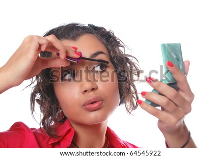 beauty girl looks in mirror and paints eyelashes with black ink - stock photo