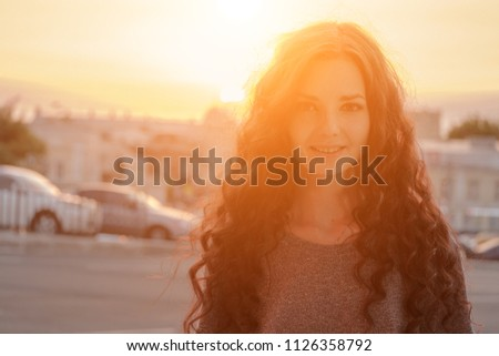Beauty Girl Outdoors enjoying city evening time. Beautiful Teenage Model girl with long hair in Sun Glow . Free Happy Woman. Image Toned in warm color