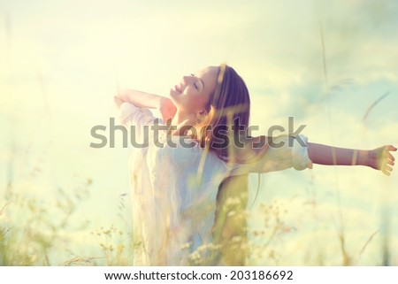 Beauty Girl Outdoors enjoying nature. Beautiful Teenage Model girl in white dress having fun on summer Field with blooming flowers, Sun Light. Sunrise. Glow Sun. Free Happy Woman - stock photo