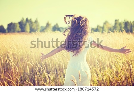 Beauty Girl Outdoors enjoying nature. Beautiful Teenage Model girl in white dress running on the Spring Field, Sun Light.  - stock photo