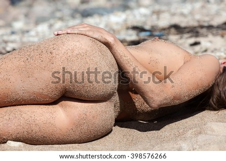 Beauty Girl Outdoors enjoying nature. Healthy lifestyle concept. Young naked woman covered by sand resting on a sandy beach near the sea - stock photo