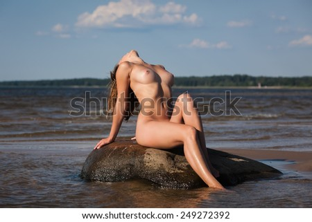 Beauty girl outdoors enjoying nature. Young naked woman on the beach - stock photo