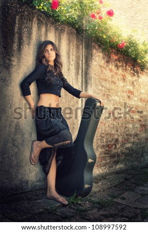 Beauty girl playing guitar outside - stock photo