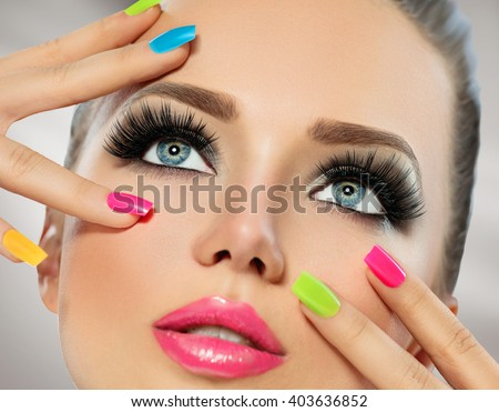 Beauty Girl Portrait with Vivid Makeup and colorful Nail polish. Colourful nails. Fashion Woman portrait close up. Bright Colors. Manicure Make up. Smoky eyes, long eyelashes. Rainbow Colors  - stock photo
