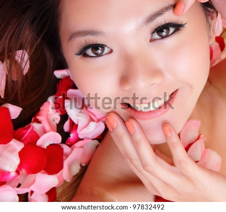 beauty Girl smiling face and hand touch her face close up with red rose background, model is a asian beauty - stock photo