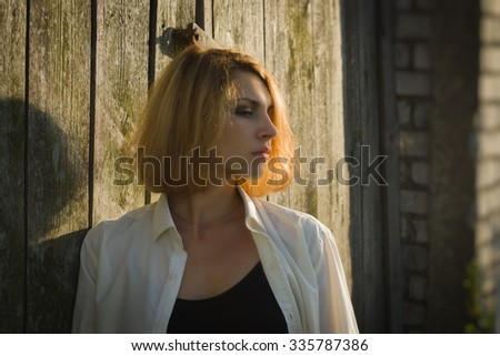 Beauty girl  standing against a background of a wooden barn