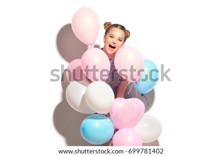 Beauty girl with colorful air balloons laughing, isolated on white background. Beautiful Happy Young woman on birthday holiday party. Joyful model having fun and celebrating with pastel color balloon.