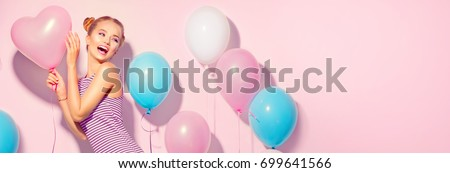 Beauty girl with colorful air balloons laughing over pink background. Beautiful Happy woman on birthday party. Joyful model having fun, playing and celebrating with pastel color balloons. Wide screen.