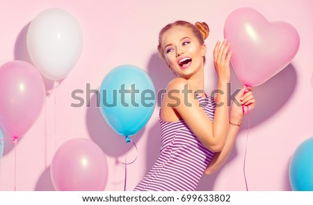 Beauty girl with colorful air balloons laughing over pink background. Beautiful Happy Young woman on birthday holiday party. Joyful model having fun, playing and celebrating with pastel color balloon