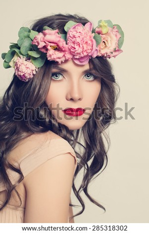 Beauty Girl with Flowers Hairstyle. Beautiful Young Woman Portrait with Summer Pink  Peony Flowers. Long Permed Curly Hair and Fashion Makeup - stock photo
