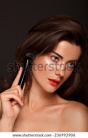 Beauty Girl with Makeup Brush. Bright Holiday Make-up for Brunette Middle Age Woman with green Eyes. Orange and Yellow Make up. Beautiful Face. Makeover. Perfect Skin. Applying Makeup - stock photo