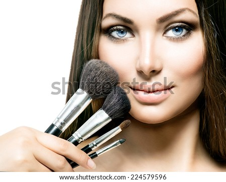 Beauty Girl with Makeup Brushes. Natural Make-up for Brunette Woman with Blue Eyes. Beautiful Face. Makeover. Perfect Skin. Applying Makeup  - stock photo