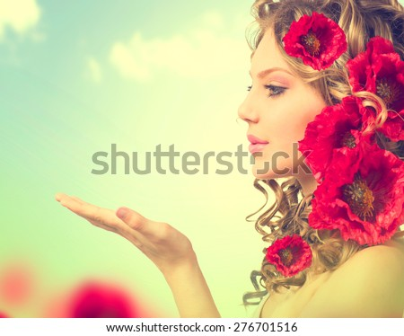 Beauty girl with red poppy flowers hairstyle and open hands. Blowing flower. Hairstyle with flowers. Fantasy girl portrait over blue sky outdoor. Summer fairy portrait. Long permed hair - stock photo