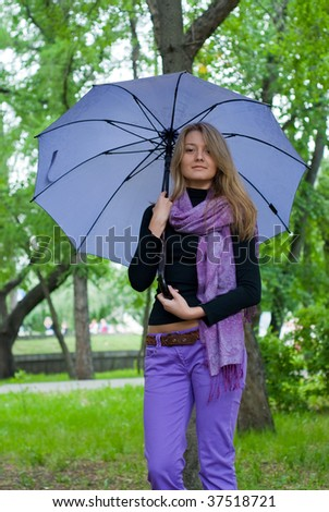 beauty girl with umbrella and violet scarf in the park on trees background - stock photo