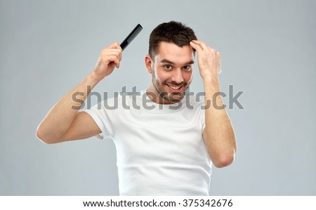 beauty, grooming and people concept - smiling young man brushing hair with comb over gray background - stock photo