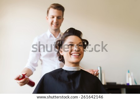 beauty, hairstyle and people concept - happy young woman with hairdresser with hair spray fixating hairdo at salon - stock photo
