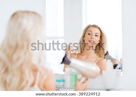 beauty, hairstyle, morning and people concept - smiling young woman with fan blow drying her hair looking to mirror at home bathroom - stock photo