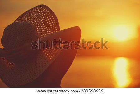 beauty happy woman in her hat is back and admire the sunset over the sea on the beach - stock photo