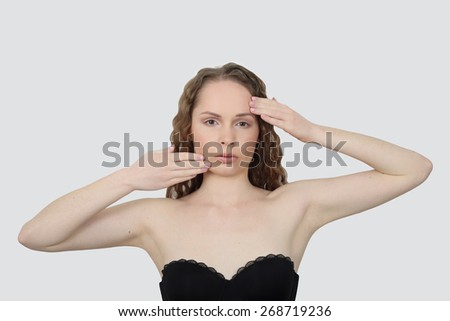 Beauty, health, make up and skin care concept - Young woman makes facial massage on gray background - stock photo