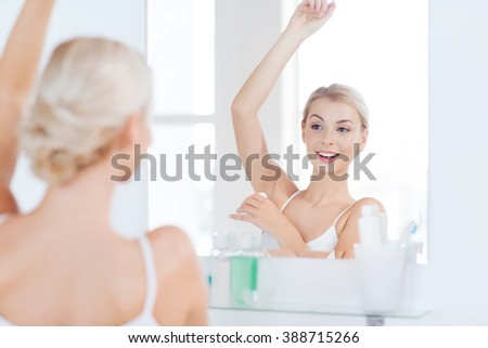 beauty, hygiene, morning and people concept - smiling young woman applying antiperspirant or stick deodorant and looking to mirror at home bathroom - stock photo