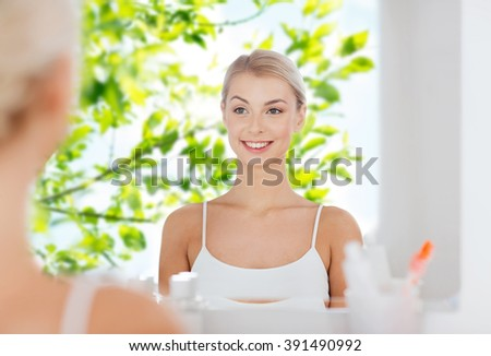 beauty, hygiene, morning and people concept - smiling young woman looking to mirror at home bathroom over green tree leaves natural background - stock photo