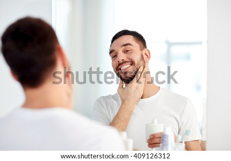 beauty, hygiene, shaving, grooming and people concept - smiling young man looking to mirror and applying aftershave at home bathroom