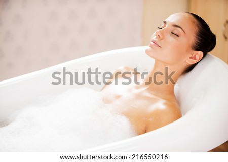 Beauty in bubble bath. Side view of attractive young woman keeping eyes closed while enjoying luxurious bath  - stock photo