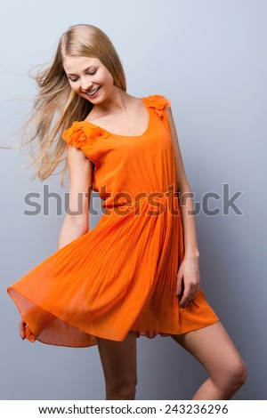 Beauty in motion. Beautiful young woman in pretty dress posing against grey background   - stock photo
