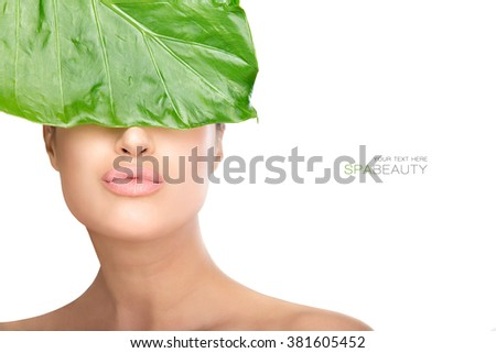 Beauty in spa concept with a gorgeous natural woman holding a fresh green leaf to her eyes while sending a kiss to camera. Closeup portrait isolated on white with copyspace for text - stock photo