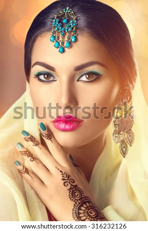 Beauty Indian woman portrait. Brunette Hindu model girl with brown eyes, mehendi tattoo on her hand and national Indian jewels looking in camera. Indian girl in sari. Traditions - stock photo