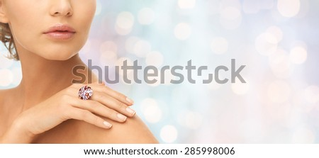 beauty, jewelry, people and accessories concept - close up of woman with cocktail ring on hand over blue holidays lights background - stock photo