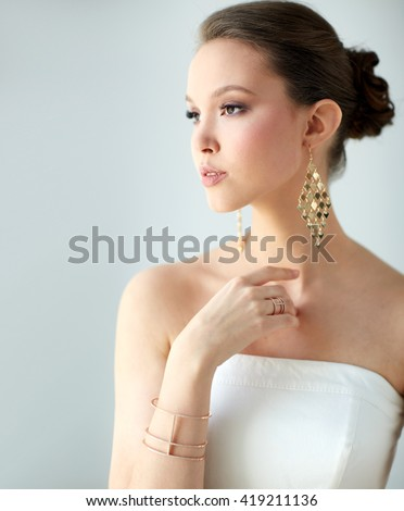 beauty, jewelry, wedding accessories, people and luxury concept - beautiful asian woman in white dress or bride with golden earrings and bracelet - stock photo