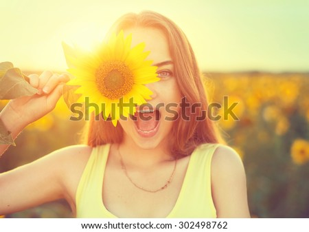 Beauty joyful teenage girl with sunflower enjoying nature and laughing on summer sunflower field. Sunflare, sunbeams, glow sun. Backlit. - stock photo