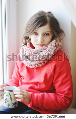 Beauty kid girl girl sitting by the window with a cup of hot drink  in warm colorful  clothes - stock photo
