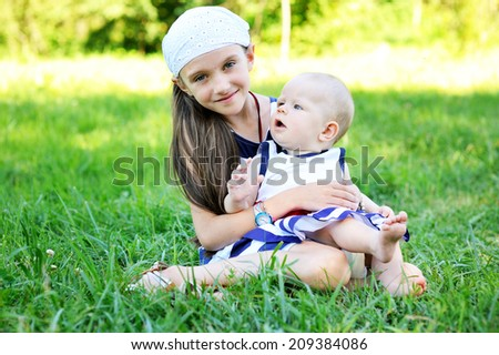 Beauty kid girl hugs her baby sister on the green lawn at the sunny day