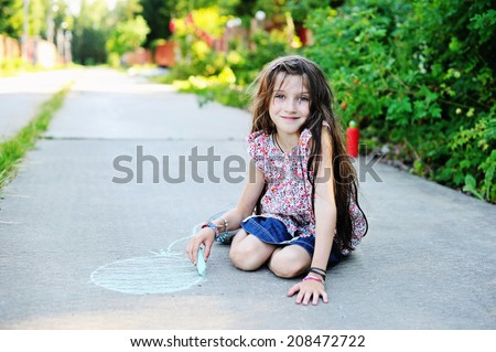 Beauty kid school age girl drawing with chalks on the road in the sunny summer evening