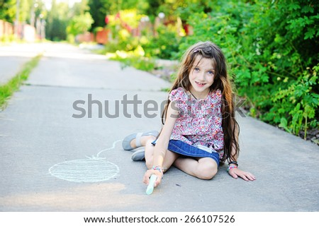 Beauty kid school age girl drawing with chalks on the road in the sunny summer evening - stock photo