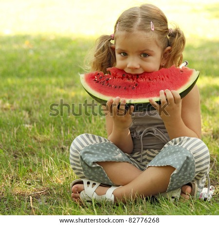 beauty little girl eat watermelon in park
