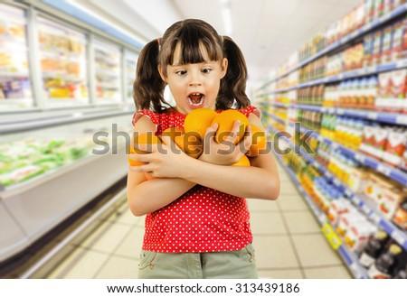 beauty little girl hold many orange and amazed, on shop background - stock photo