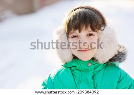 Beauty little girl in fur headphones and jacket has fun outdoors  on perfect  sunny winter day